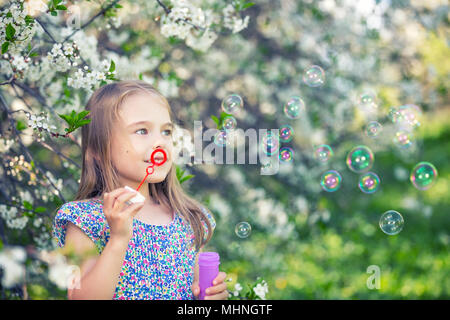 Little girl blowing soap bubbles in cherry blossom garden - Stock Photo