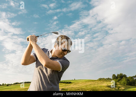 Close up of young man swinging a golf club - Stock Photo