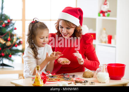 Mother and daughter baking Christmas cookies at decorated tree. Mom and child bake Xmas sweets. Family with kids celebrating Christmas at home. - Stock Photo