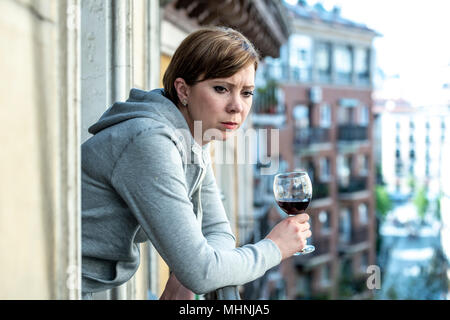 Beautiful red haired caucasian woman suffering from depression holding a glass of wine on a balcony at home. Staring out feeling sad, pain and grief.  - Stock Photo