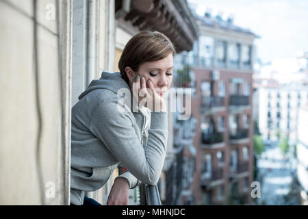 Young attractive, unhappy sad caucasian woman suffering from depression looking thoughtful on the balcony at home. In depressed and anxiety female con - Stock Photo