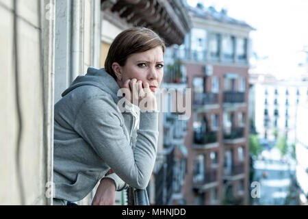 Young attractive, unhappy sad caucasian woman suffering from depression looking thoughtful and worried on the balcony at home. In depressed and anxiet - Stock Photo