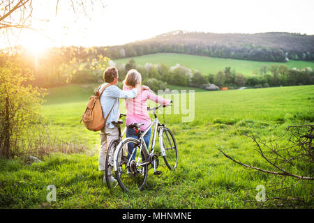 Beautiful senior couple with bicycles outside in spring nature. - Stock Photo