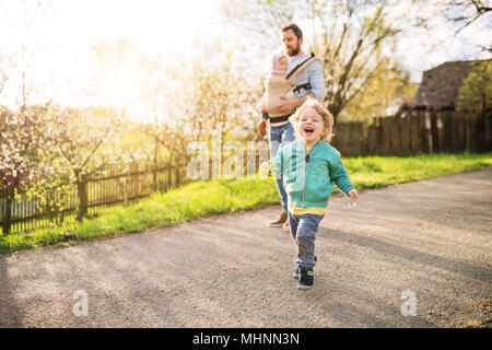 A father with his toddler children outside on a spring walk. - Stock Photo