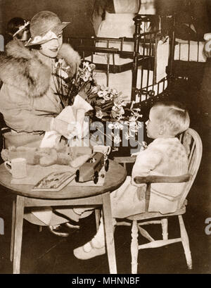 Elizabeth, Duchess of York (later Elizabeth, the Queen Mother 1900-2002) visiting St. Mary's Hospital, three years after she had laid the foundation stone for the new Medical School (see picture: 11936580). In this charming picture she can be seen talking to a little boy in one of the Nursery wards.     Date: 1934 - Stock Photo