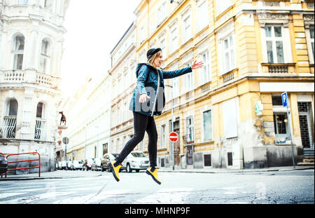 Young woman jumping on the street in town. - Stock Photo