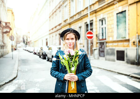 Young woman with flowers in sunny spring town. - Stock Photo