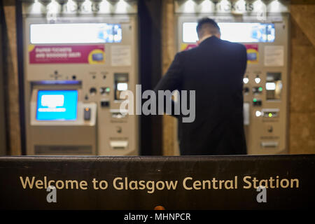Glasgow in Scotland, buying a late night ticket machine at central station - Stock Photo
