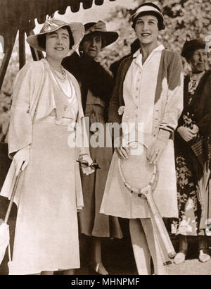 Elizabeth, Duchess of York (later Elizabeth, the Queen Mother 1900-2002) and Helen Wills Moody (1905-1998) at the Lawn Tennis Championships at Wimbledon. Princess Marie Louise of Schleswig-Holstein (1872-1956) stands behind the     Date: 1935 - Stock Photo