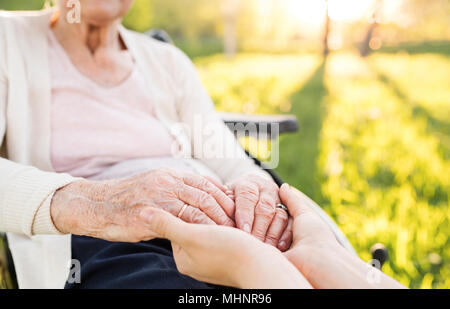 Elderly grandmother in wheelchair with granddaughter in spring nature. - Stock Photo
