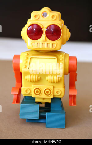 Retro Toy Walking Plastic Robot with yellow body, big red eyes, orange arms and blue feet. - Stock Photo