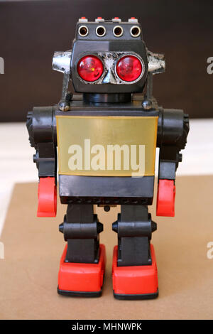 Retro Toy Walking Plastic Robot with grey body, big red eyes and red feet. - Stock Photo