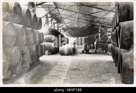 Scene in the Gonzalez Byass warehouse, export dock, Spain -- barrels stacked up ready for transport.      Date: circa 1930s - Stock Photo