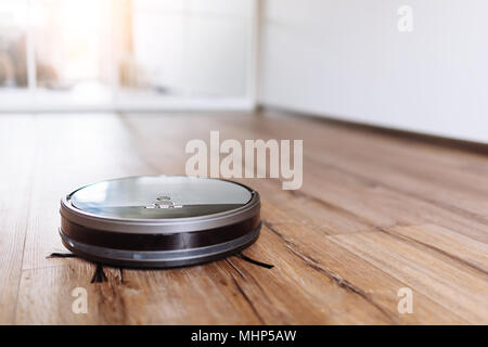 Robotic vacuum cleaner on laminate wood floor smart cleaning technology. Selective focus. - Stock Photo