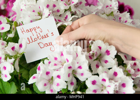 Front view of womans hand holding greeting card for Mother's day, Beautiful fresh flowers in background - Stock Photo