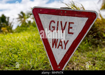 old wood give way road sign on grass - Stock Photo