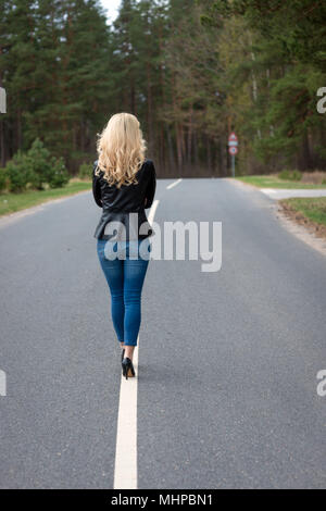 Woman from behind. A young blond woman goes through the asphalt road. - Stock Photo