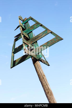 Old green sea mark used for naval navigation isolated on blue sky. - Stock Photo