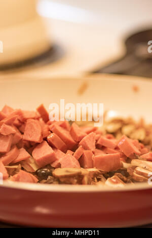 Red and white frying pan full of sliced sausage, black olives, mushrooms and chopped red onion. - Stock Photo