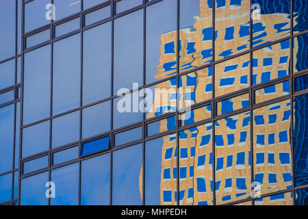 Warped view of reflected building seen in the glass and metal of opposing skyscraper. - Stock Photo