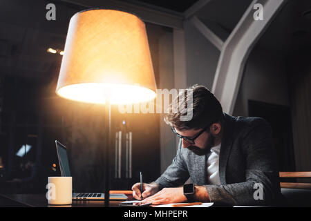 Bearded businessman sits by the wooden table with lamp and working on new startup project in loft ofiice at night. Young coworker using modern gadgets - Stock Photo