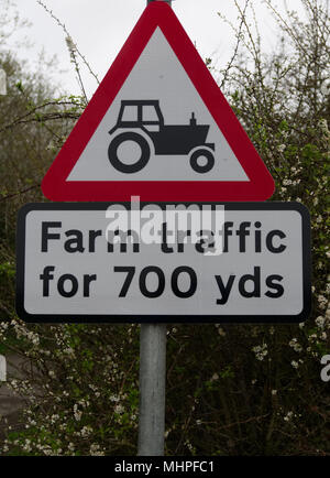 Red and white triangular road safety sign warning of farm traffic with picture of black tractor for 700 yards - Stock Photo