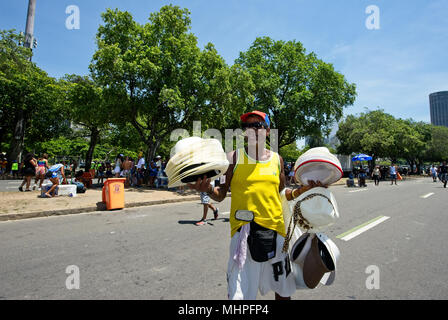 South America, Brazil - February 11, 2018: A street vendor sells hats, visors and caps during carnival in Rio de Janeiro - Stock Photo
