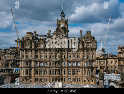 Rocco Forte Balmoral Hotel, Princes Street, Edinburgh, UK, with blue sky and construction cranes. Workmen in orange abseiling to clean windows - Stock Photo