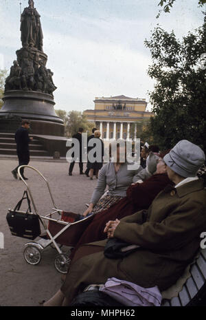 People sitting on a bench, Leningrad (St Petersburg), USSR, with a statue of Catherine the Great on the left and the Alexandrinsky Theatre in the background.       Date: circa 1960s - Stock Photo