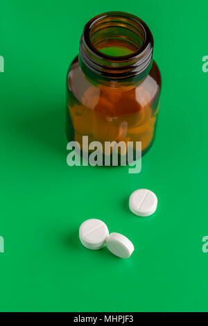 Glass pills bottle from white tablets on green background - Stock Photo