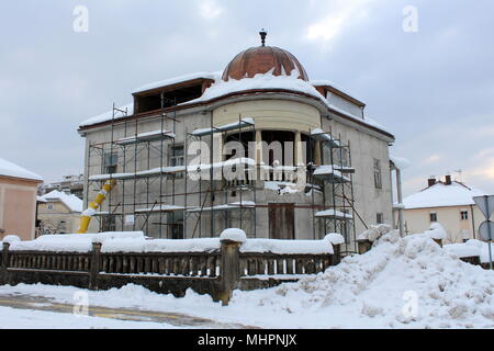 Reconstruction of old suburban house with new exterior surrounded with building scaffolding and covered in deep snow during cold winter - Stock Photo