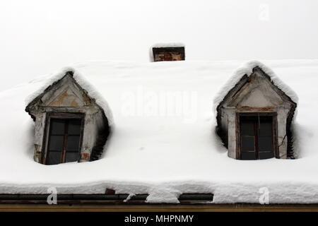 Two roof windows on old abandoned house with small chimney in background covered with deep white snow on cold winter day - Stock Photo