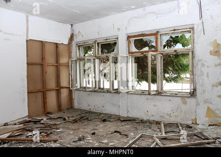 Room in abandoned building with broken windows, destroyed floorboards and dilapidated wall insulation - Stock Photo