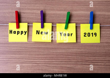 Happy New Year 2019 on notes hanging by clothespins - Stock Photo