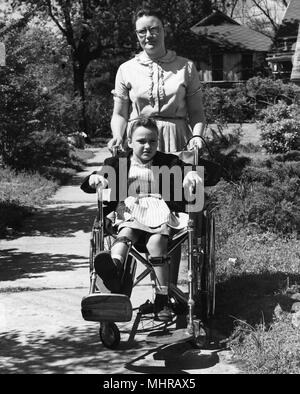 Young woman pushes a child in a wheelchair, image used to encourage individuals to receive polio vaccinations, 1968. Image courtesy Centers for Disease Control (CDC). () - Stock Photo