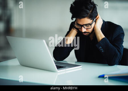Tired and worried indian business man at workplace in office - Stock Photo