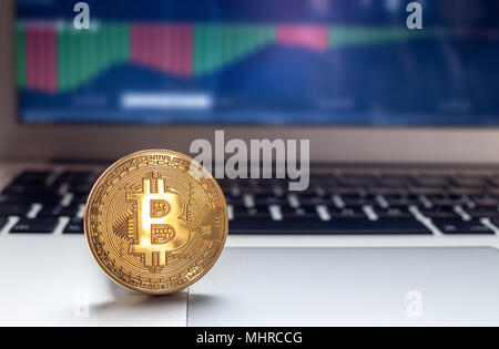 Physical Bitcoin placed on Laptop computer with charts on screen - Stock Photo