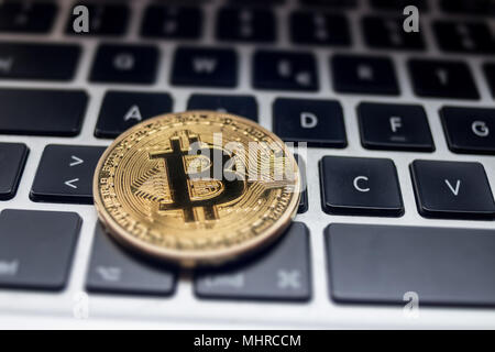 Physical Bitcoin placed on laptop computer keyboard - Stock Photo