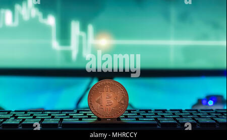Physical Bitcoin placed on Laptop computer with charts on screen, dark themed - Stock Photo