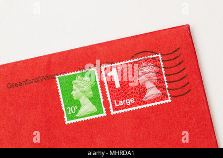 Envelope corner with 2 stamps, ones red, one green, of Queen Elisabeth II. UK postage stamp on red paper. - Stock Photo