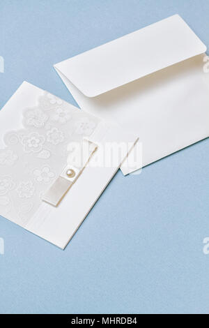 White wedding invitation with flowers lace illustration and white ribbon on light blue paper background. Vertical shot. Cute and beautiful elements. - Stock Photo