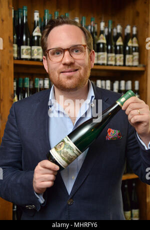 01 May 2018, Trier, Germany: Winzer Maximin von Schubert (r), from Moselweingut Maximin Grünhaus, showing a bottle of Riesling wine 'Das Kapital' (lit. The Capital). The wine originates from the vineyard of Karl Marx' Family. The Marx family has owned more than two hectares of vines for about 30 years. Photo: Harald Tittel/dpa - Stock Photo