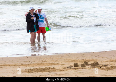 Bournemouth, Dorset, UK. 3rd May 2018. UK weather: cool sunny afternoon at Bournemouth beaches, as visitors enjoy the sunshine at the seaside. Senior couple having fun in the sea with man carrying buckets. Credit: Carolyn Jenkins/Alamy Live News - Stock Photo