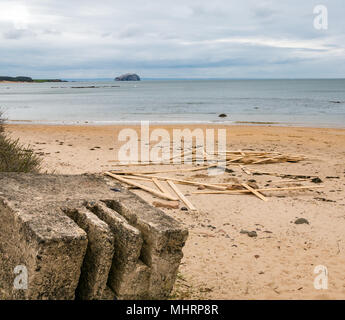 Ravensheugh Sands, East Lothian, Scotland, United Kingdom, May 2nd 2018.  A very dull grey day. Noone on the beach with a worn concrete World War II coastal defence road block, looking across the Firth of Forth towards the Bass Rock, home to the world's largest Northern gannet colony. Planks of timber still lie washed up after spilling from cargo vessel 'Frisian Lady' which lost the timber bundles during severe weather on 2nd March during the 'Beast from the East' - Stock Photo