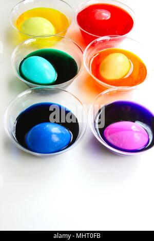 A bright and colorful image of eggs being dyed for Easter. Colored dyes in clear cups with egg in each one, different colors, isolated on white. - Stock Photo