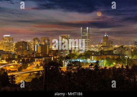 Full moon rising over Portland Oregon downtown cityscape at night