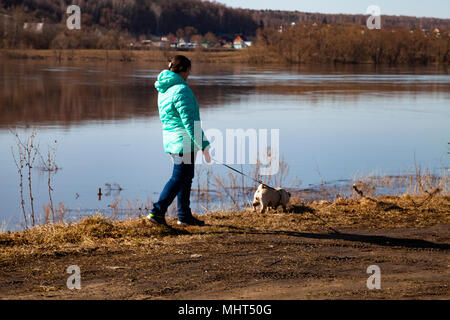 Woman with a dog walks on the riverbank on a spring day. Leisure. - Stock Photo