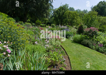 A lawned path leading through herbaceous borders, Coton Manor Gardens, Northamptonshire, UK - Stock Photo