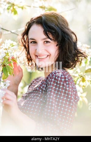 natural beauty, environment, walking concept. among blooming white flowers of cherry trees there is darkhaired amaizing woman with radiant smile and brown eyes - Stock Photo