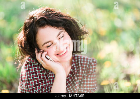 work, busy, spring concept. among yellow flowers of garden there is business woman who is talking on the smartphone, she is smiling and feeling comfortable sitting on the grass - Stock Photo